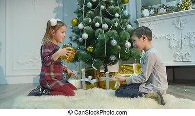 little brother and sister unpack gifts. The concept of Christmas and New Year