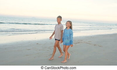 Little brother and sister walking along the beach
