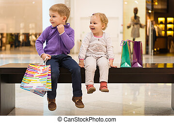 Little brother and sister with shopping bags sitting on bench