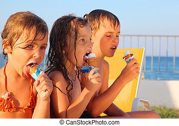 little brother and two sisters in swimsuits on beach eating...