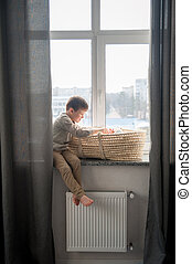Little brother is sitting near the window with himnewborn sister in the cradle. Children with small age difference.