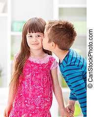 Little brother kissing his sister