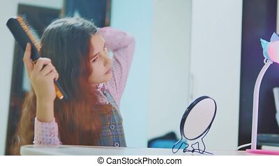 little brunette girl combing her hair looks in mirror....