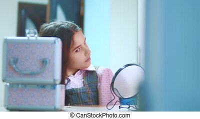 little brunette girl combing her hair looks in the mirror....