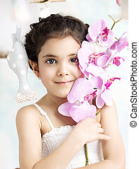 Little brunette girl holding a flower