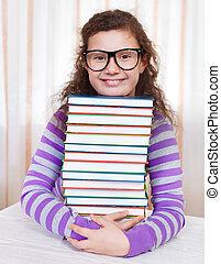 Little brunette smiling girl with books