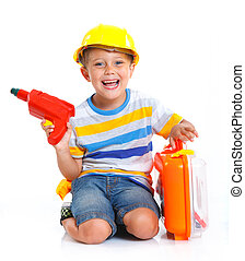 Boy in a helmet plays in the builder