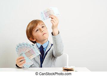 Little businessman calculates money. Children's economic education. Money and savings concept.