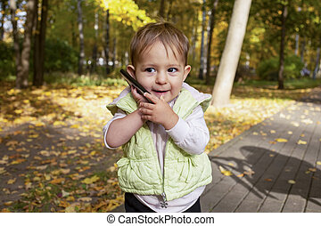 little businessman. portrait of cute toddler playing talking on a smartphone.