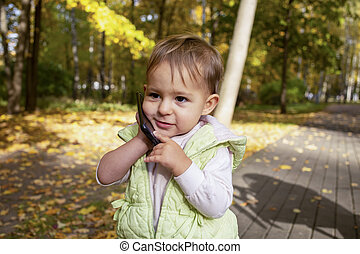 little businessman. portrait of cute toddler playing talking on a smartphone