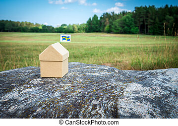 Little cardboard house in Swedish summer landscape