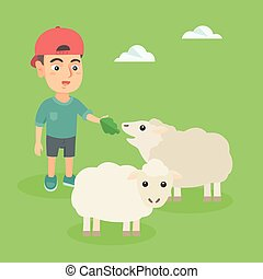 Little caucasian boy feeding a sheep with salad.