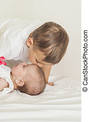 Little Caucasian Boy Kissing His Newborn Sister. Indoors Shot.