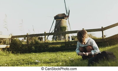Little Caucasian boy playing near rustic windmill. Happy kid...