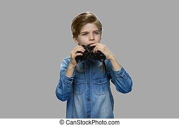 Little caucasian boy using binoculars.