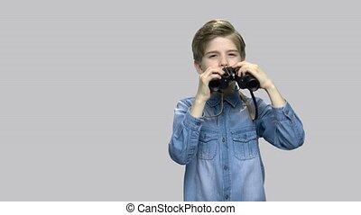 Little caucasian boy using binoculars. Cute boy in denim...