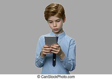 Little caucasian boy using smartphone on gray background.