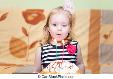 Little Caucasian girl blowing two candles on birthday cake