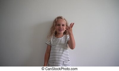 Little caucasian girl counting her fingers over white background. Gimbal shot