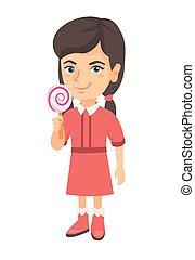 Little caucasian girl holding a lollipop candy.