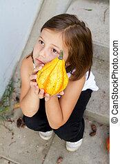 little, caucasian girl holding pumpkin in her hands