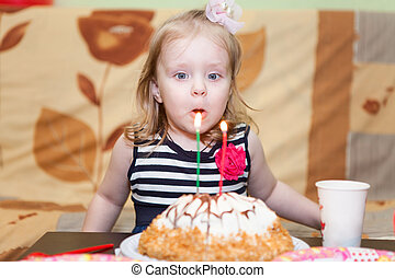 Little Caucasian girl two ears blowing candles on birthday cake