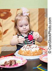 Little Caucasian girl two ears eating birthday cake