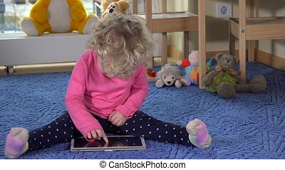 Little caucasian girl using tablet pc sitting on blue carpet