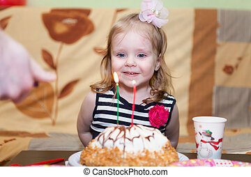 Little Caucasian girl with flame on candles at birthday cake