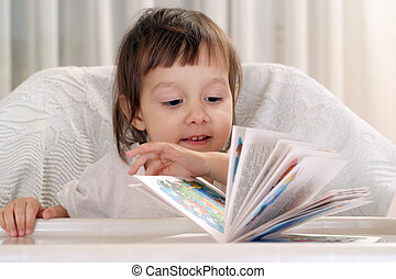Little Caucasian poppet sitting at a table with a book on a light background