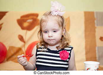 Little Caucasian with fork in hand in domestic room