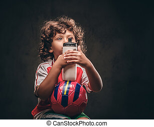 Little champion boy in sportswear holds a ball and bottle with water. Isolated on the dark textured background.