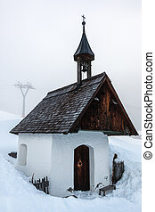 Little chapel and snow in the mountains