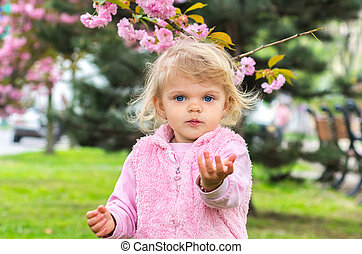 little charming blonde playing with pleasure in the garden with blooming cherry blossom