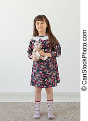 Little charming girl in a flower dress gently embraces her favorite toy bunny standing on a white background. The concept of children's toys and goods
