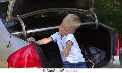 Little cheerful boy sitting in the trunk of the car and shows a thumbs up.