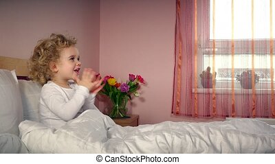 Little cheerful child girl clap hands and get gift present...
