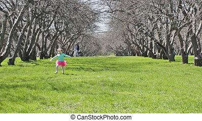little cheerful girl runs on park in the direction of the camera