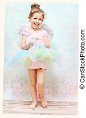 Little cheerful girl with white wings