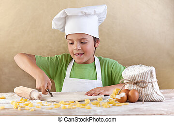 Little chef cutting the dough making pasta