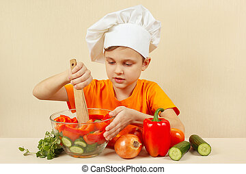 Little chef mixing the vegetables in bowl with salad