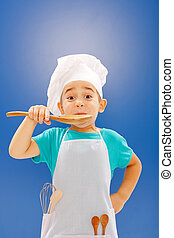 Little chef tasting food from wooden spoon on blue ...