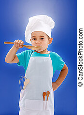 Little chef tasting food from wooden spoon on blue...