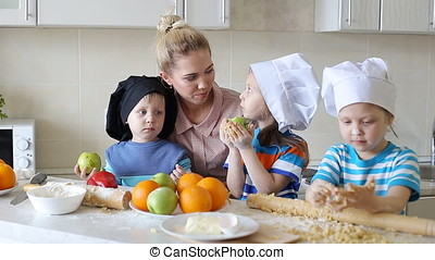 little chefs learn to cook. mother with children in the...
