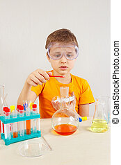 Little chemist in safety goggles studies chemical practice in laboratory