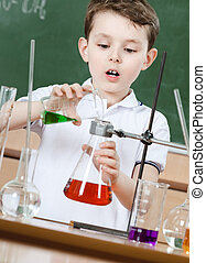 Little chemist pours colored liquid in conical flask holding an experiment