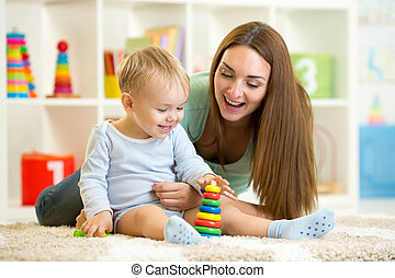 little child and his mommy playing with toys