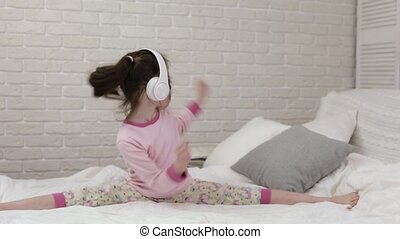 little child baby girl listening to the music with headphones
