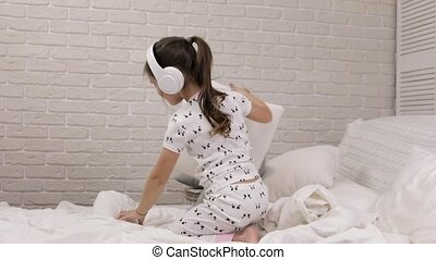 little child baby girl listening to the music with...