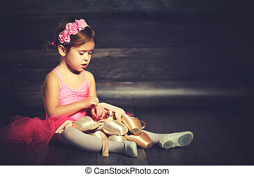 little child ballerina with ballet pointe shoes and pink skirt tutu